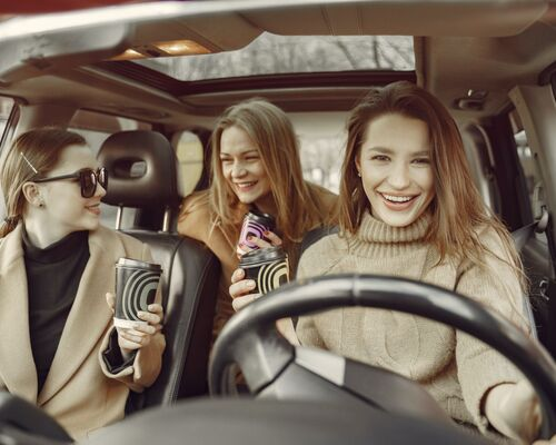 friends-driving-around-city-with-coffee-4005053