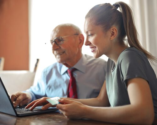 young-woman-helping-senior-man-with-payment-on-internet-3823488